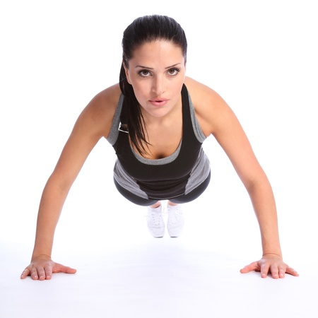 athletic body: Fit beautiful and young athletic woman doing push up exercises on floor, wearing a grey and black sports outfit. Stock Photo