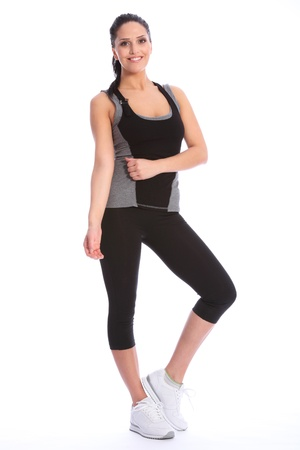 lycra: Fit beautiful and young athletic woman standing in a relaxed pose, big smile and wearing a grey and black sports outfit with white trainers.