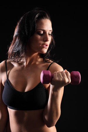 black bra: Bicep curl by beautiful young caucasian woman working out with fitness hand weights, wearing black sports bra, taken against black background.