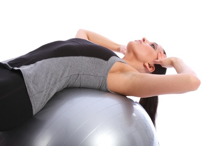 straining: Abdominal stomach crunches exercise by beautiful young caucasian woman in gym leaning back on fitness exercise ball. She is wearing a grey and black sports outfit. Stock Photo