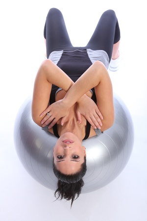 straining: Balance exercise by beautiful young caucasian woman lying back on fitness exercise ball with arms crossed over chest. She is wearing a grey and black sports outfit.