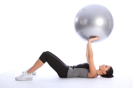 lying on back: Beautiful athletic young caucasian woman lying on her back working triceps brachii muscles with a fitness exercise ball. She is wearing a grey and black sports outfit.