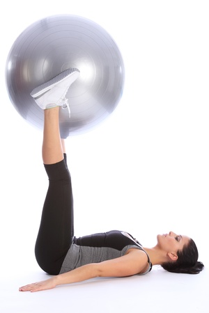 Fit beautiful young woman concentrates hard lying on the floor lifting exercise ball using her legs as part of workout routine. She is wearing a grey and black sports outfit with white trainers. photo