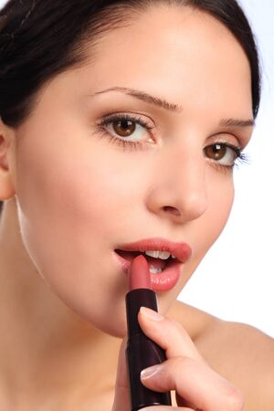 Close up beauty shot of young woman applying lipstick to lips with mouth open. photo