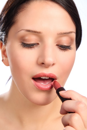 Beauty shot of young woman applying lipstick make up to lips with mouth open. photo