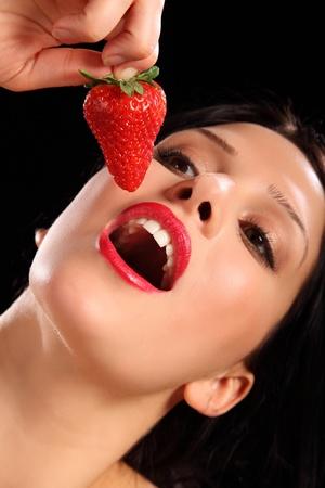 Hermosa mujer joven sexy usando l�piz labial rojo brillante como ella abre la boca para comer fruta fresca de fresa. Foto de archivo