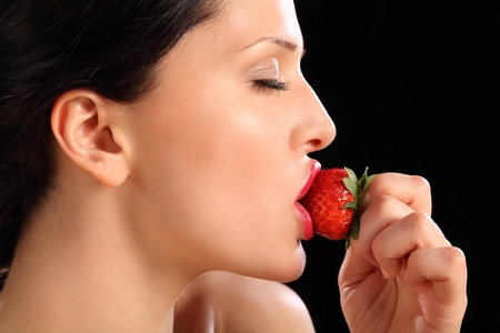 Beautiful sexy young girl wearing bright red lipstick, eyes closed as she eats fresh healthy strawberry fruit. photo