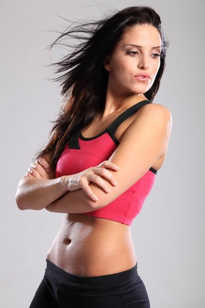 black bra: Fit beautiful young woman posing in pink and black fitness outfit of sports bra and black track bottms. Model has long black hair.