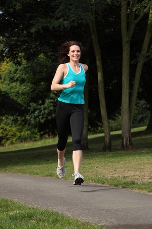 lycra: Fit beautiful young woman running in the park. She is wearing black jogging leggings and blue sports vest outfit. Stock Photo