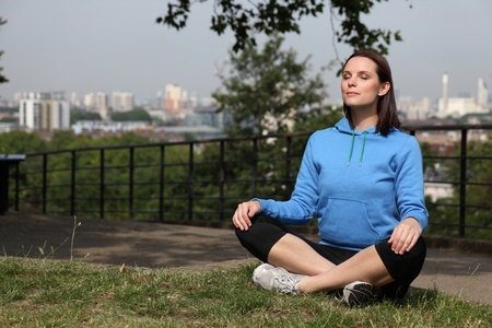 Fit beautiful young athletic woman sitting cross legged in the park, meditating during exercise routine. She is wearing black jogging leggings and blue sports hoodie, behind her is a city backdrop. photo