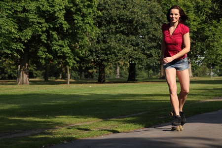 sexy shorts: Fit beautiful young athletic woman roller skating through the park with a big happy smile. She is wearing a red top and denim cut off shorts showing off her long legs.