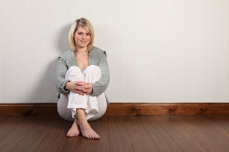cardigan: Beautiful young caucasian woman with blonde hair and happy smile sitting on laminate floor at home, relaxing bare foot. She is wearing white linen pants and a grey heavy knit cardigan. Stock Photo