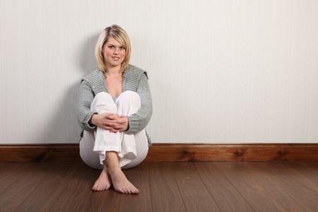 pied fille: Belle jeune caucasienne femme avec des cheveux blonds et sourire joyeux assis sur stratifiés à la maison, détente pied nu. Elle porte des pantalons de lin blancs et un cardigan tricot lourd gris.