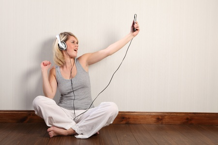 Sitting cross legged on laminate floor at home a beautiful young blonde caucasian girl dances and sings to music on her personal mp4 player. She is bare foot in white linen trousers and grey vest. photo