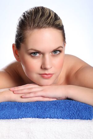 Beautiful young naked woman, lying on her front in health spa for beauty treatment. Models head is resting head on blue towel and looking straight into camera with clear blue eyes. photo