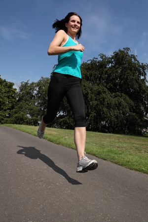 lycra: Summer time exercise for happy beautiful young athlete girl training by running in the park sunshine under a blue sky. She is wearing black jogging leggings and blue sports vest outfit.