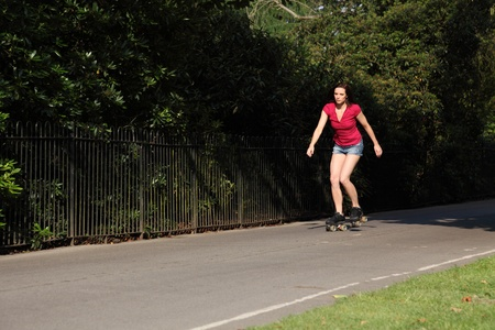 Leisure activity for fit beautiful young athletic woman roller skating through the park in summer sunshine. She is wearing a red top and denim cut off shorts showing off her long legs. photo