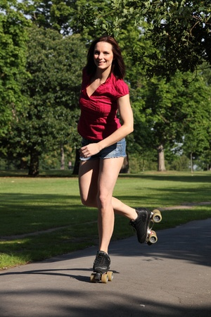 Fun leisure activity for fit beautiful young athletic woman roller skating through the park in summer sunshine. She is wearing a red top and denim cut off shorts showing off her long legs. photo