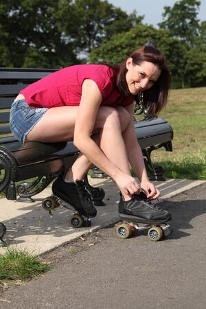 Fun leisure activity for beautiful young long legged girl putting on her roller skates sitting on park bench in summer sunshine. She is wearing a red top and denim cut off shorts. Stock Photo - 10103431