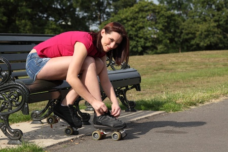 Fun leisure activity for beautiful young long legged girl putting on her roller skates sitting on park bench in summer sunshine. She is wearing a red top and denim cut off shorts. photo