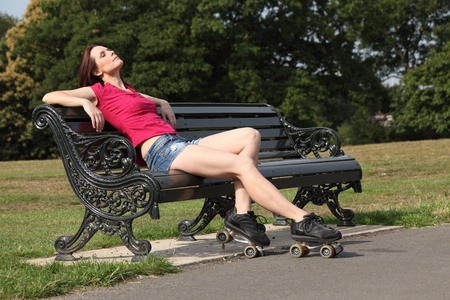 Sitting on park bench a beautiful young woman with long legs wearing roller skates relaxes with her eyes closed, enjoying the warm summer sunshine. She is wearing a red top and denim cut off shorts. photo