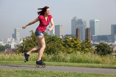 Summer fun in London for beautiful young sexy woman, roller skating through the park with a big happy smile, against the cityscape backdrop of London, England United Kingdom. photo