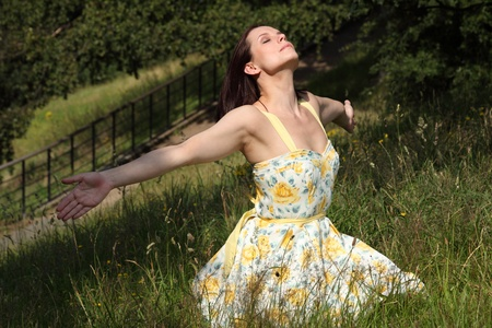 outstretched arms: Beautiful young caucasian woman sitting on grass in countryside, head upturned arms out with eyes closed soaking up the sunshine. She is wearing yellow summer dress.