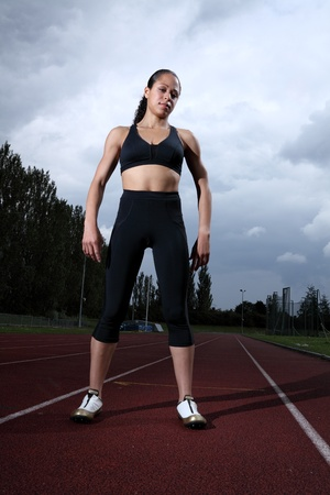 Beautiful fit young female athlete standing on running track wearing black lycra sports outfit and running spikes. Grey cloudy sky in background. photo