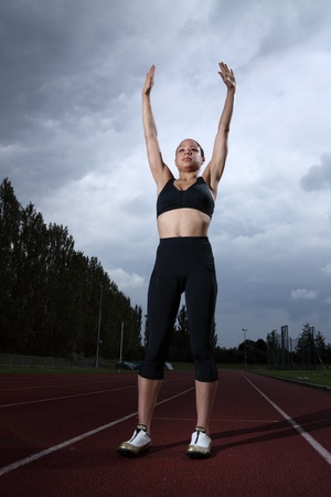 Arms raised in success for beautiful fit young female athlete standing on running track wearing black lycra sports outfit and running spikes. Grey cloudy sky in background. photo