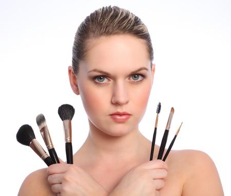 Hermosa rubia joven conforman artista con ojos azules con conjunto de pinceles de maquillaje seis. Los tipos de pincel son polvo colorete Fundaci�n o base, separador de azote de ojo, cejas sombra de ojos y ojo liner pincel.