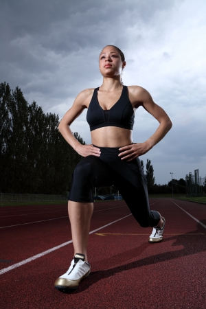 Warm up thigh stretch by fit young athlete girl on running track wearing black lycra sports outfit and running spikes. Grey cloudy sky in background. photo