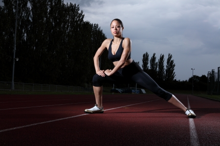 Fitness warm up stretch for beautiful young athlete woman on athletics running track wearing black lycra sports outfit and running spikes. Dark grey cloudy sky in background.