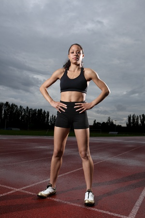 runner girl: Beautiful fit young female athlete standing on running track wearing black lycra sports outfit and running spikes. Grey cloudy sky in background. Stock Photo