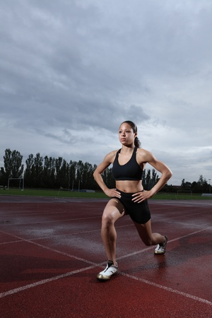 Warm up lunge exercise for quadriceps by fit young female athlete on athletics running track, wearing black lycra sports outfit and running spikes. Grey cloudy sky in background. photo