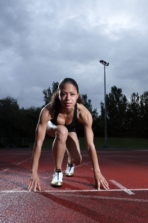 to crouch: Starting position crouch by fit young female athlete on athletics running track, wearing black lycra sports outfit and running spikes. Grey cloudy sky in background. Stock Photo