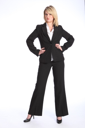 Confident and serious in business suit, a full body shot of beautiful young blonde business woman, standing with hands on hips.