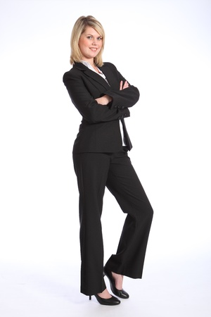 Confident and smiling in business suit, a full body shot of beautiful young blonde business woman, standing with arms folded.