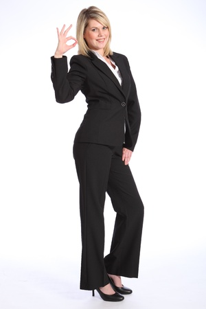 Confident and smiling in business suit, a full body shot of beautiful young blonde business woman, standing giving the universal okay sign with fingers on right hand. photo