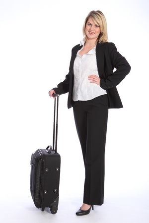 First class business travel with a beautiful young blonde woman wearing a smart black suit, standing in a relaxed pose waiting with a suitcase. photo