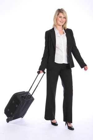 First class business travel for a happy beautiful young blonde woman wearing a smart black suit, walking and pulling her suitcase. photo
