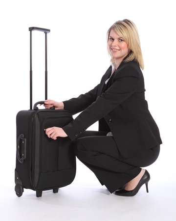 First class business travel for a happy, beautiful young blonde woman wearing a smart black suit, crouching down to open her suitcase. photo