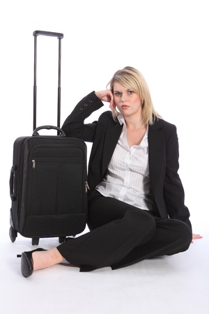 First class business travel for a beautiful young blonde woman wearing a smart black suit. She has a serious expression and is sitting on floor with her suitcase. photo