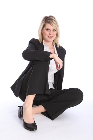 Beautiful young blonde business woman wearing a smart black suit, sitting relaxed and confident on the floor. photo