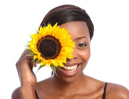 Beautiful young African American girl with huge happy smile, holding a bright yellow sunflower up to her face. Taken against a white background. photo