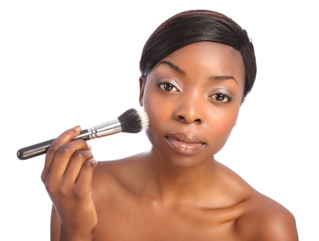 Beautiful young african american woman applying make up using stippling brush also referred to as a cosmetics powder brush. photo
