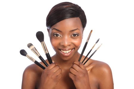 Beautiful young African American beautician woman holding set of six make up brushes. Brush types are powder blusher foundation or base, eye lash separator, brow eye shadow and eye liner brush. photo