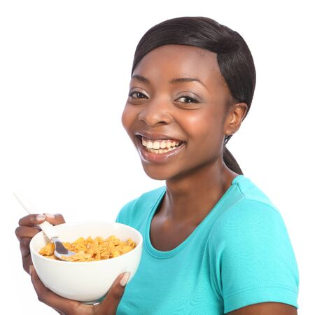 Beautiful young African American girl with huge happy smile, eating morning breakfast cereal. Taken against a white background. photo