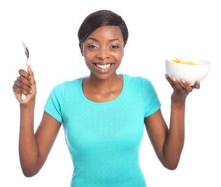 Beautiful young black woman with huge happy smile, holding breakfast cereal of cornflakes in a bowl, and a spoon in other hand. Taken against a white background. photo