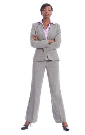 full suit: Serious and confident young african american business woman, full length shot standing in grey suit with arms folded.