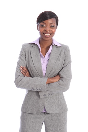 Confident and smiling in grey business suit, a portrait shot of beautiful young black business woman, standing with arms folded. photo